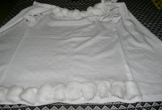 stitching cotton balls to white t-shirt to make shaun the sheep costume for kids